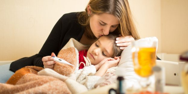 Portrait of young caring mother kissing sick daughter in head